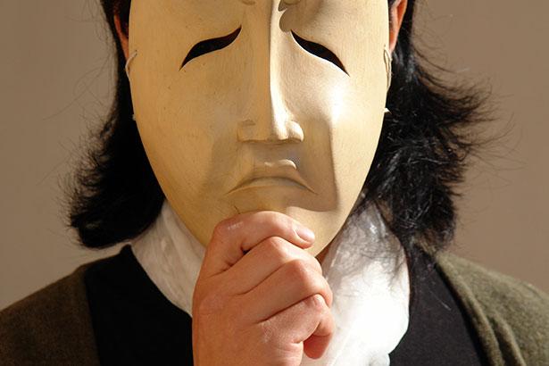 Eine Frau in Trauer hält eine weinende Holzmaske vor das Gesicht