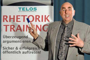 Referenten Dr. Elmar Teutsch Vortrag Rhetorik Flipchart Anzug grau Hemd Krawatte Filzstift Hand gespreizt Schrift Rhetorik Training D06846gp4nn