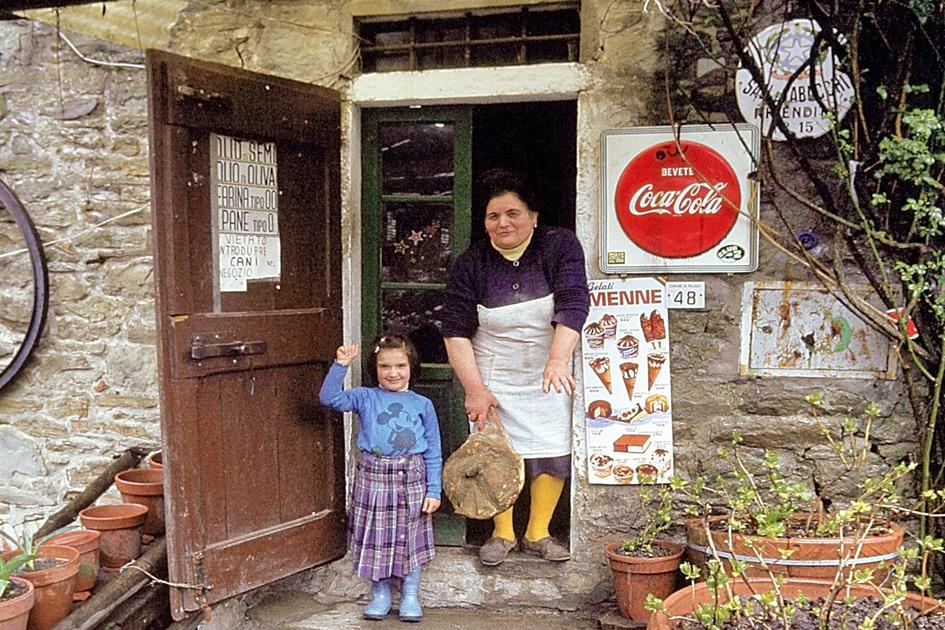 Frau und Kind winken aus einem alten Lebensmittelgeschäft in der Toscana Italien