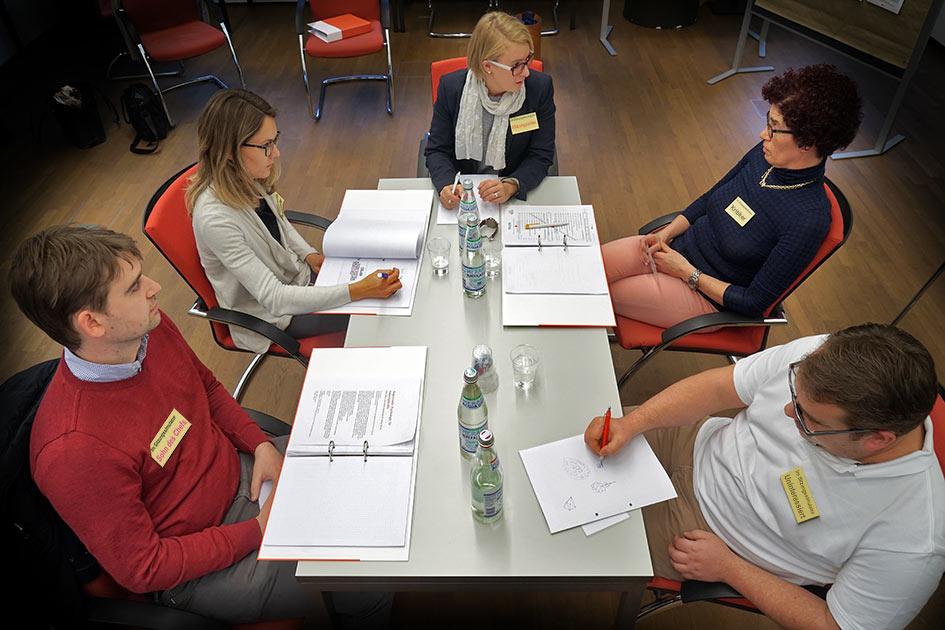 Sitzungssimulator Gruppe Sitzungsleiterin Tisch ernst skeptisch Namensschilder / Foto: TELOS - E9696bt