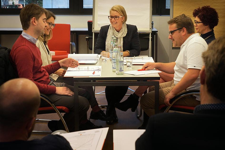 Sitzungssimulator Gruppe Sitzungsleiterin Tisch lächeln Beobachter / Foto: TELOS - E9706bdo