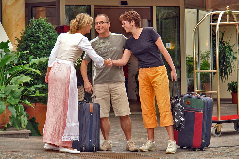 Hotel Begrüßung Wirtin Dirndl Trachtenmode Gäste Paar Koffer Eingang lachen Händedruck / Foto: TELOS - B2757b
