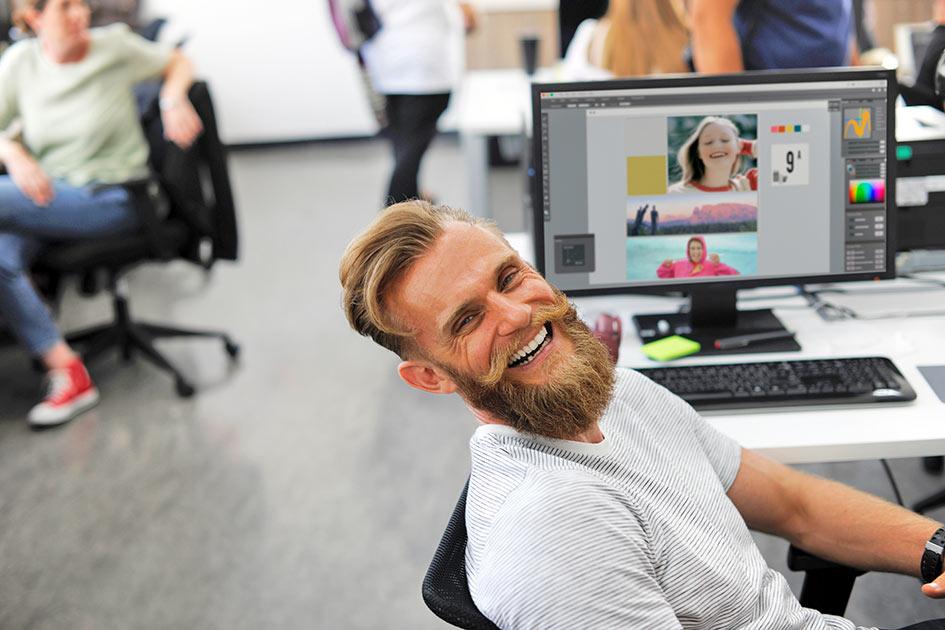 Büro Mitarbeiter Mann Bart lachen Blick Computer Grafik Fotos / Kollage: TELOS - 2815