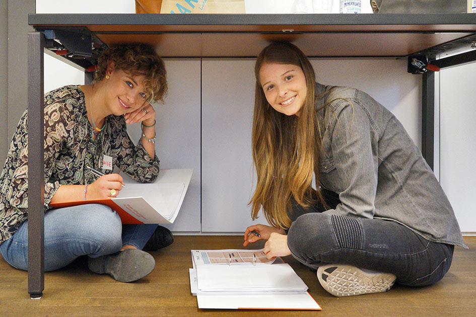 Kreativitätstraining seltsam sitzen 2 Frauen texten unterm Tisch lachen Blick / Bildbearbeitung: TELOS - E4603b