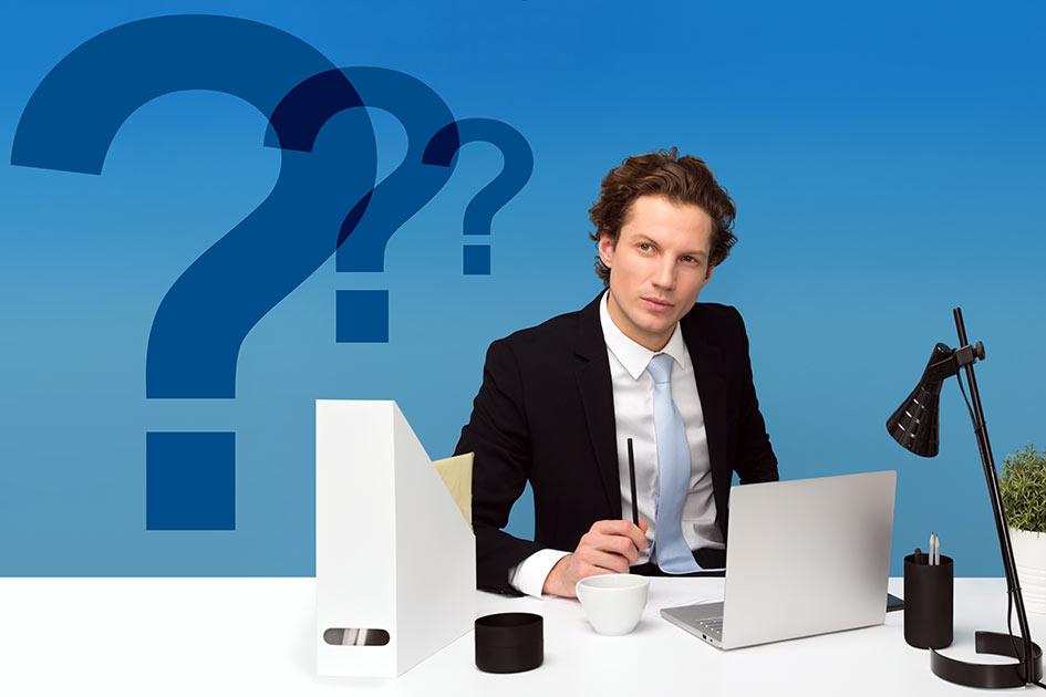 Mann jung Schreibtisch Büro Computer Labtop Akten unsicher neu in der Führung Fragezeichen / Grafik: TELOS - 2813bc