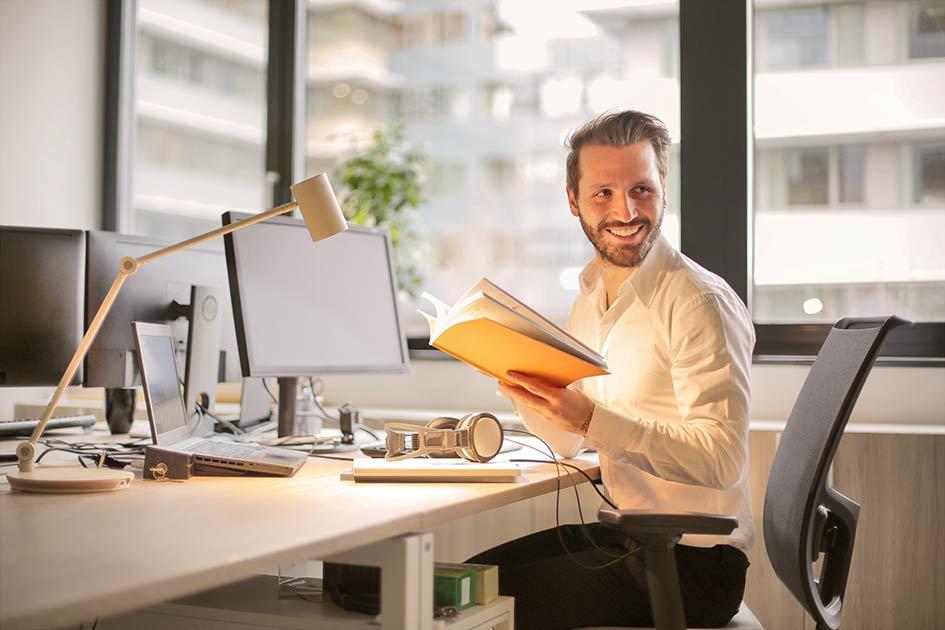 Mann jung Schreibtisch Computer Labtop Headset Mappe lachen / Grafik: TELOS - 927022