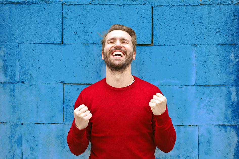 Mann lachen Fäuste ballen Pullover rot Mauer blau Erfolg Freude / Bildbearbeitung: TELOS - 2842