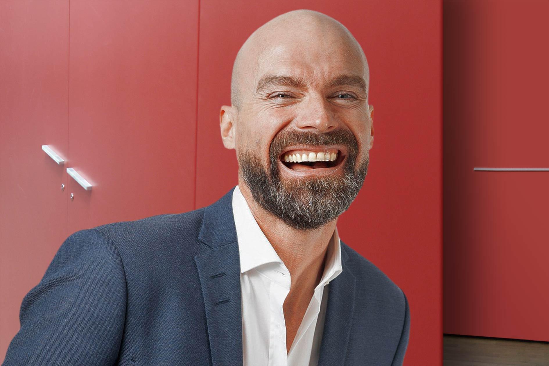 Seminare Führung Management Mann Anzug lachen Blick Büro rot / Grafik: TELOS - 2812bw
